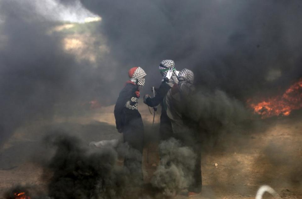 Palestinian protesters stand in smoke billowing from burning tyres during a demonstration along the border with the Gaza strip east of Gaza city on June 1, 2018.