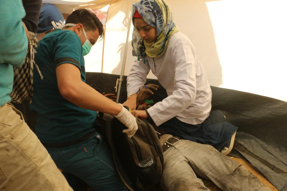Paramedic Razan Al-Najar (right), seen here earlier helping a wounded Palestinian, was killed on Friday by an Israeli sniper while helping wounded Palestinians in Khan Younis, Gaza on June 1, 2018.