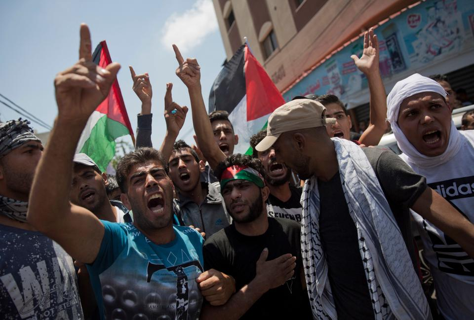 Palestinian mourners chant angry slogans during the funeral of a volunteer paramedic Razan Najjar, 21, in Khan Younis, Ssouthern Gaza Strip, Saturday, June 2, 2018.