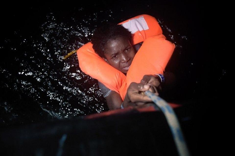 A woman holds onto a rope during a rescue operation off Libya's Mediterranean coastline. October 12, 2016. (AFP)