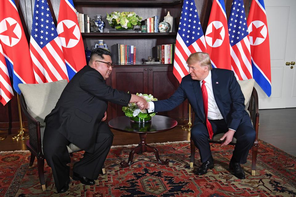 US President Donald Trump (R) shakes hands with North Korea's leader Kim Jong-un (L) as they sit down for their historic US-North Korea summit, at the Capella Hotel on Sentosa island in Singapore. Donald Trump and Kim Jong-un have become on June 12 the first sitting US and North Korean leaders to meet, shake hands and negotiate to end a decades-old nuclear standoff.