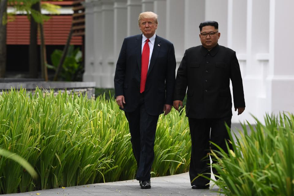 North Korea's leader Kim Jong-un (R) walks with US President Donald Trump (L) during a break in talks at their historic US-North Korea summit, at the Capella Hotel on Sentosa island in Singapore.