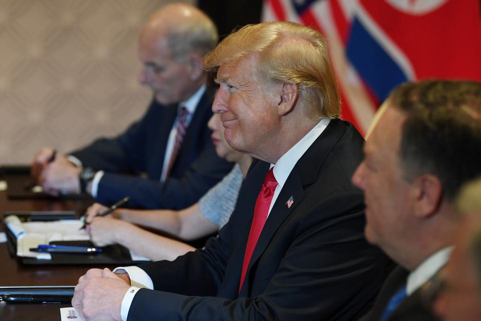 US President Donald Trump looks on while seated with members of his delegation during the US-North Korea summit with North Korea's leader Kim Jong-un (not pictured) at the Capella Hotel on Sentosa island in Singapore.