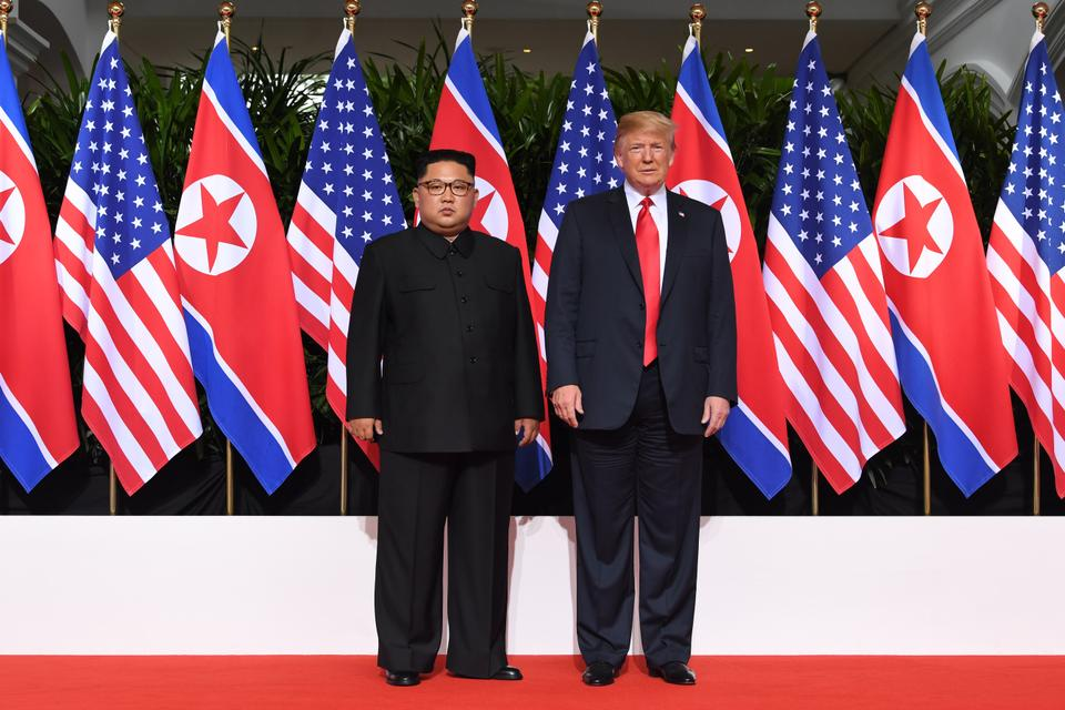 US President Donald Trump (R) and North Korea's leader Kim Jong-un (L) pose together at the start of their historic US-North Korea summit, at the Capella Hotel on Sentosa island in Singapore.