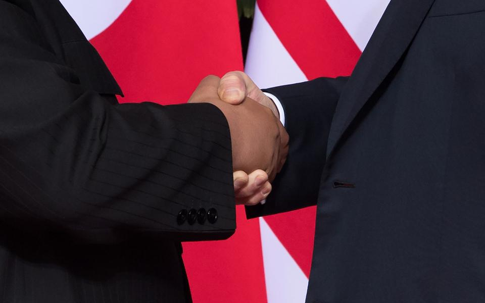US President Donald Trump (R) shakes hands with North Korea's leader Kim Jong-un (L) at the start of their historic US-North Korea summit, at the Capella Hotel on Sentosa island in Singapore.