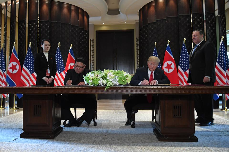 US President Donald Trump (2nd R) and North Korea's leader Kim Jong-un (2nd L) sign documents as US Secretary of State Mike Pompeo (R) and the North Korean leader's sister Kim Yo-jong (L) look on at a signing ceremony during their historic US-North Korea summit, at the Capella Hotel on Sentosa island in Singapore.