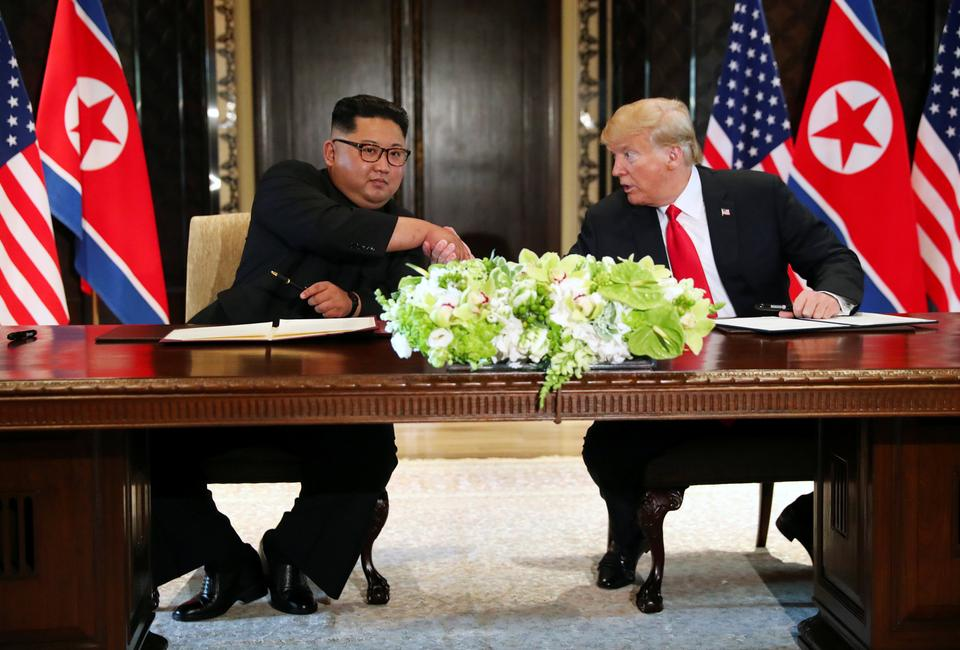 US President Donald Trump shakes hands with North Korea's leader Kim Jong-un after signing documents that acknowledge the progress of the talks and pledge to keep momentum going, after their summit at the Capella Hotel on Sentosa island in Singapore.