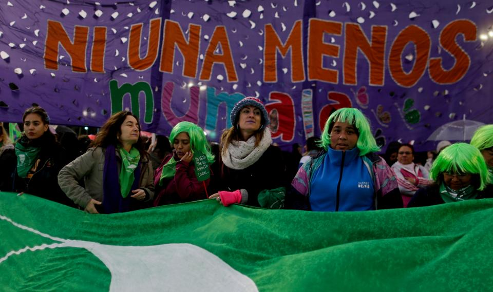 Pro-choice demonstrators stand under the Spanish message