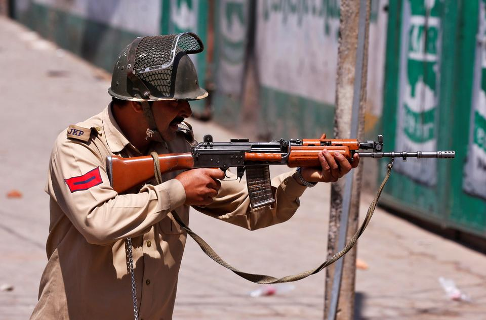An Indian police officer aims his gun towards demonstrators, during the funeral of Kaisar Ahmad Bhat, a civilian, who according to local media, was hit by a Central Reserve Police Force (CRPF) vehicle during a protest after Friday prayers, in Srinagar, June 2, 2018.