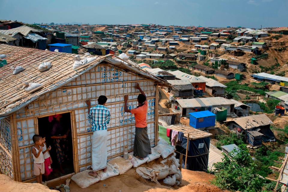In this April 28, 2018, file photo, Rohingya refugees rebuild their makeshift house, in preparation for the approaching monsoon season at the Kutupalong Rohingya refugee camp in Kutupalong, Bangladesh.