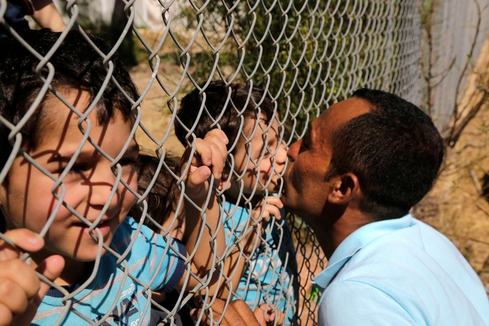 Ammar Hammasho from Edlib in Syria who lives in Cyprus, kisses one of his four children after they arrived with their mother to a refugee camp in Kokkinotrimithia, outside of the capital Nicosia, in the eastern Mediterranean island of Cyprus, on Sunday, September 10, 2017.