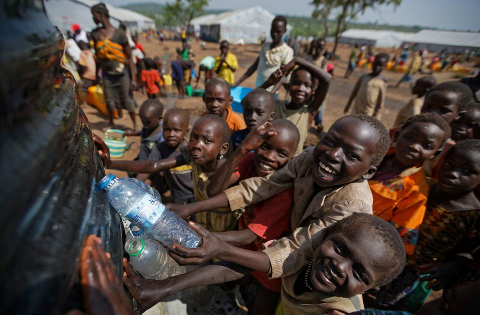 South Sudanese refugee children catch some of the water overflowing from a reservoir being filled from a truck, at the Imvepi reception centre, where newly arrived refugees are processed before being allocated plots of land in nearby Bidi Bidi refugee settlement, in northern Uganda on Friday, June 9, 2017.