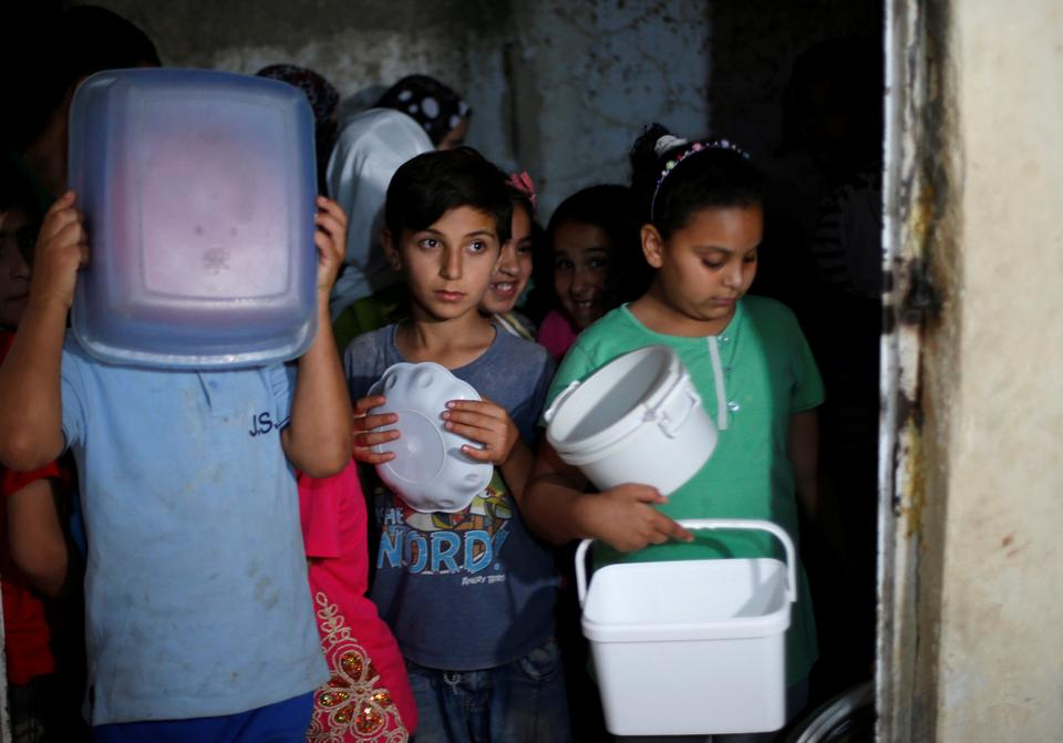 Children wait for meals provided through the initiative, Family Kitchen, which redistributes excess food from five-star hotels to underprivileged families during the holy month of Ramadan, in Al Baqaa Palestinian refugee camp, near Amman, Jordan, June 10, 2018.
