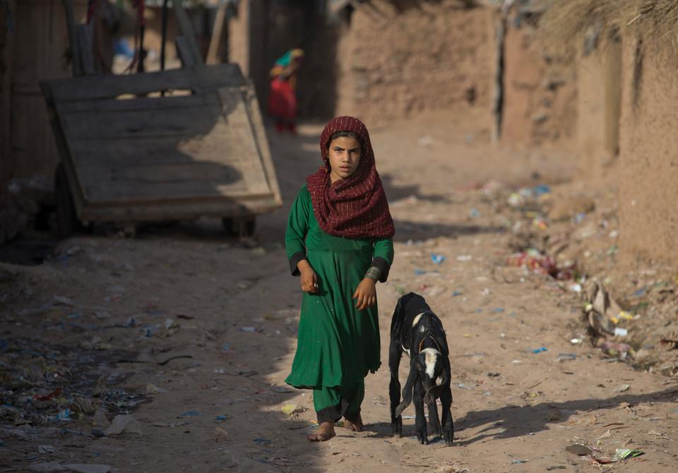 An girl from neighboring Afghanistan, who fled her village with her family due to war and famine, walks in a refugee camp, in a suburb of Islamabad, Pakistan, Tuesday, June 19, 2018.