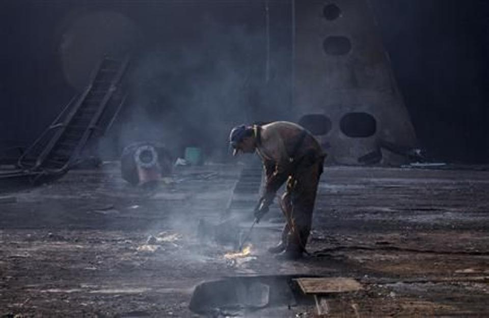 Workers in torn overalls that easily catch fire risk their lives just walking through the yard — an apocalyptic mix of rusty machinery, jagged-edged steel and giant ship engines on the oil-stained shore. (Reuters Archive)