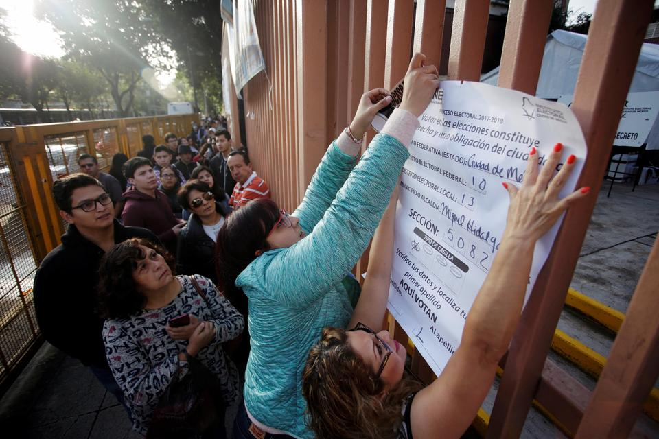 Poll workers place a sheet with the information of the polling station as people wait to cast their vote for the presidential election in Mexico City.