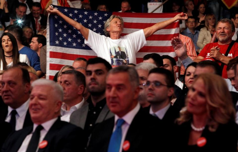 A Djukanovic supporter waves a US flag during a rally for his ruling Democratic Party of Socialist ahead of the election.