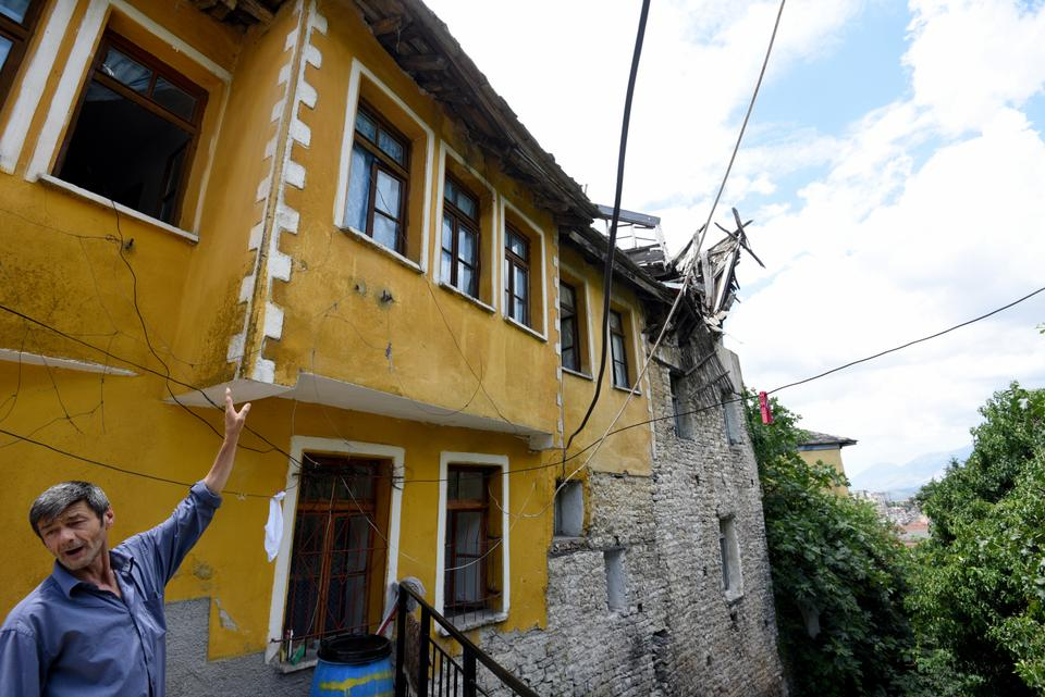 A man points to the damage to a house belonging to the Lolomani family in the UNESCO protected city of Gjirokastra.