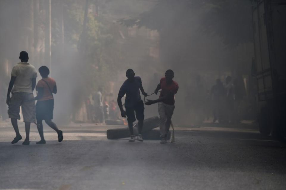 Protesters move tires to barricade a street in the Port-au-Prince suburb of Petion-Ville on July 7, 2018, to protest against the increase in fuel prices.