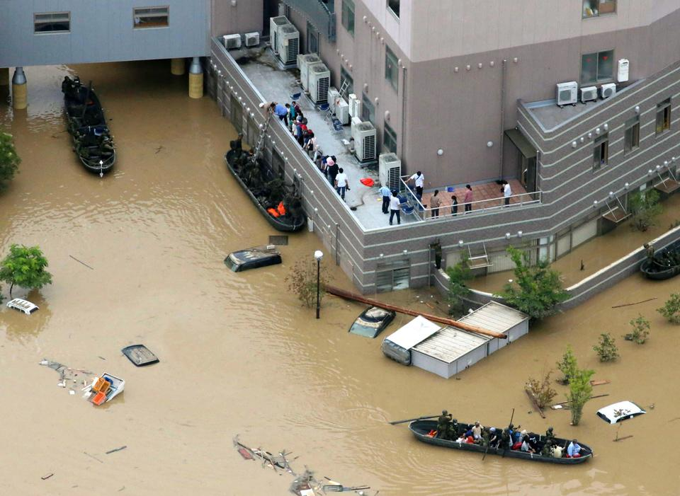 People are rescued by boats from Mabi Memorial Hospital that was isolated due to flood damage caused by heavy rain in Kurashiki, Okayama prefecture on July 8, 2018.