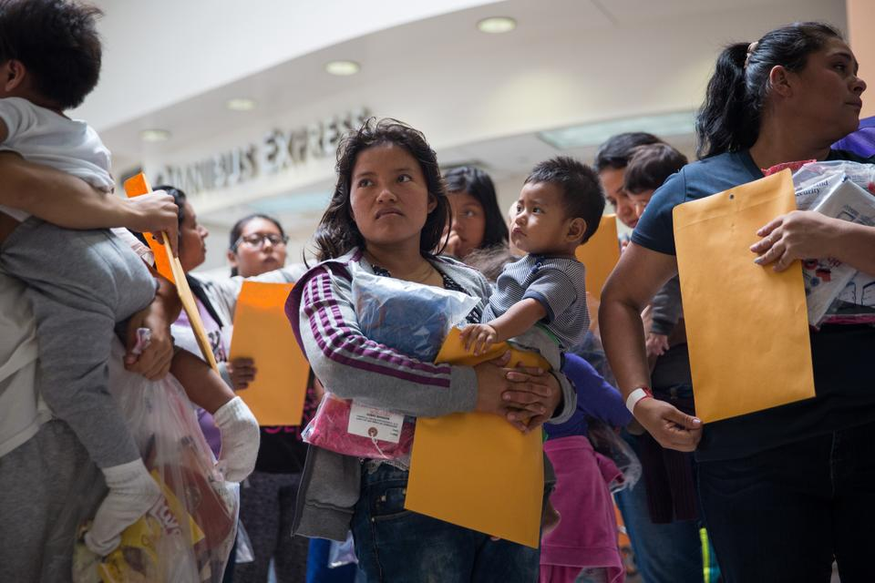 Immigrants wait to head to a nearby Catholic Charities relief centre after being dropped off at a bus station shortly after release from detention through a