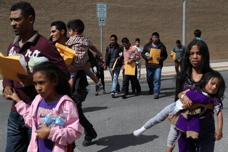 Undocumented immigrant families walk from a bus depot to a respite centre after being released from detention in McAllen, Texas, US, July 3, 2018.