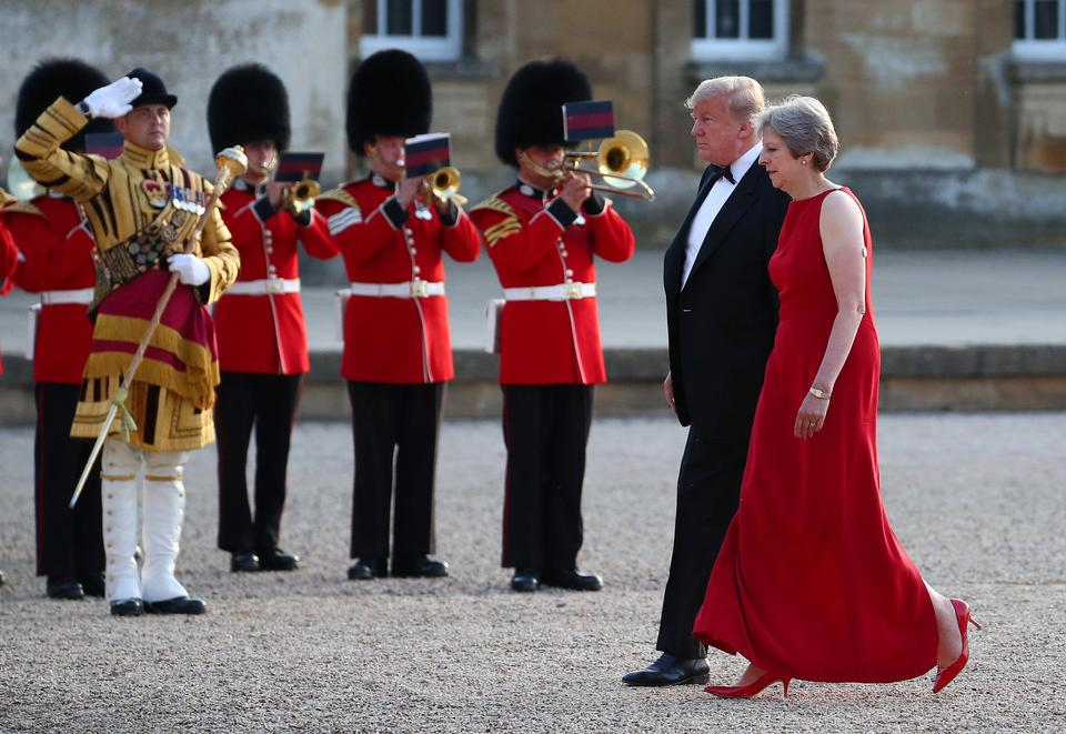 British Prime Minster Theresa May and U.S. President Donald Trump walk across the courtyard at Blenheim Palace, where they are attending a dinner with specially invited guests and business leaders, near Oxford.