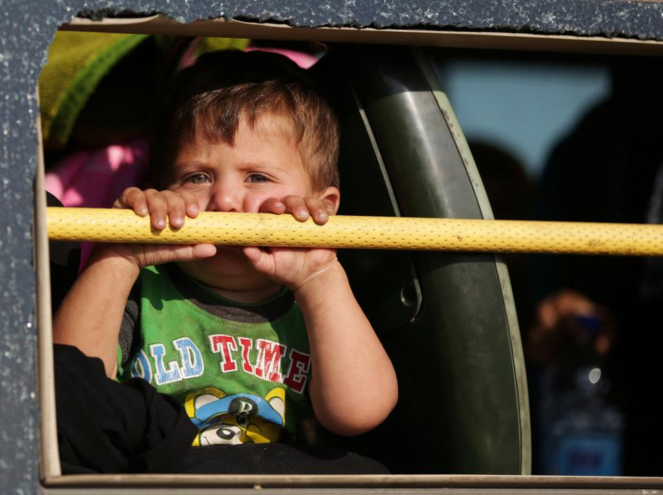 A boy looks out of a bus window upon arrival in Hama from Daraa, Syria July 21, 2018.