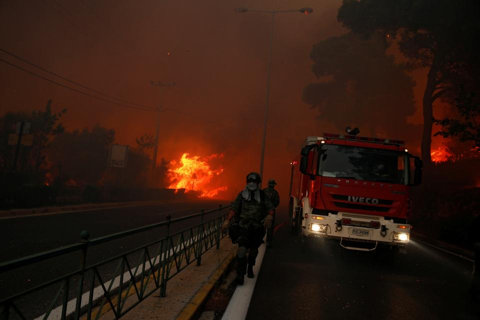 Soldiers fall back as a wildfire burns in the town of Rafina, near Athens, Greece, July 23, 2018