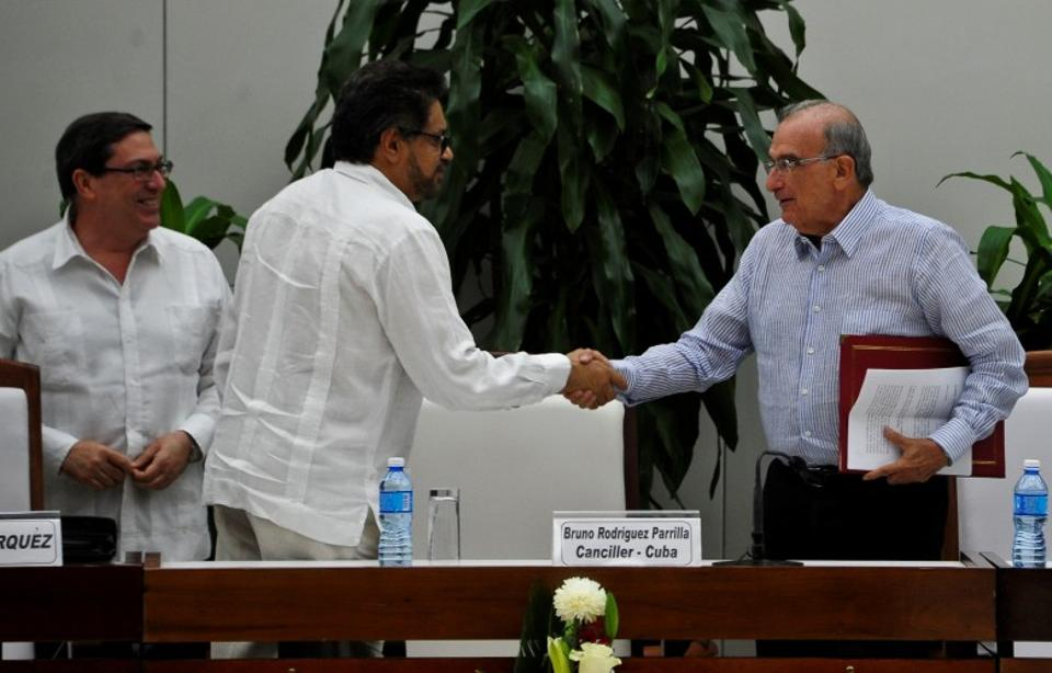 FARC-EP leftist guerrilla commander Ivan Marquez (C) and the head of the Colombian delegation for peace talks Humberto de la Calle (R) shake hands after signing a new peace agreement. (AFP Archive)