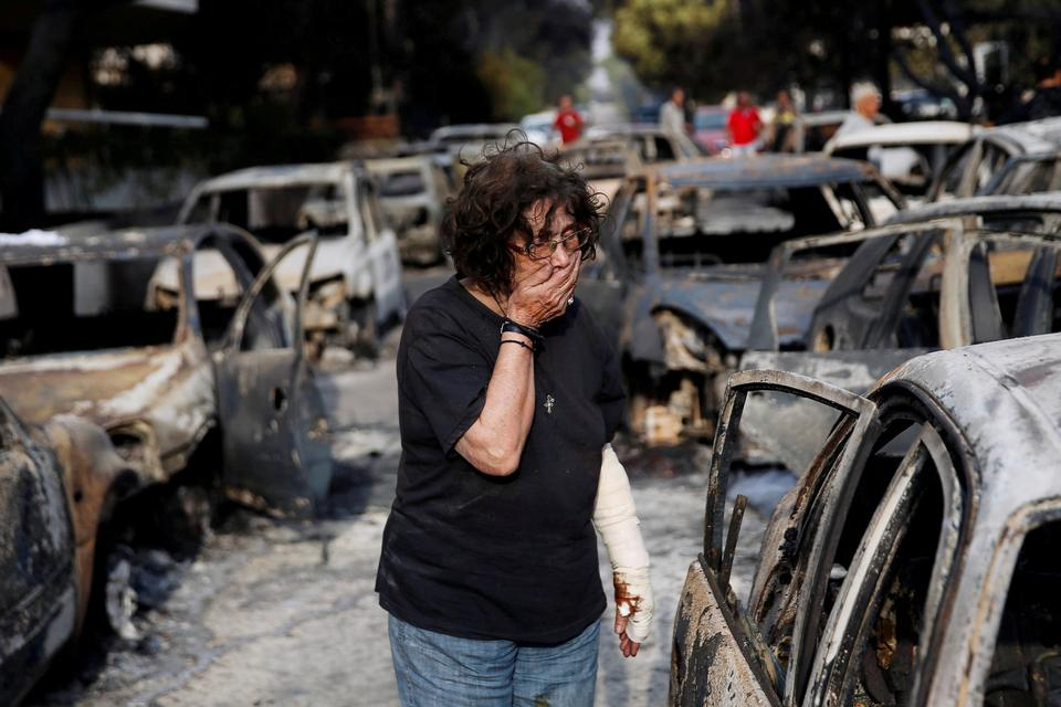 A woman reacts as she tries to find her dog, following a wildfire at the village of Mati, near Athens, Greece.