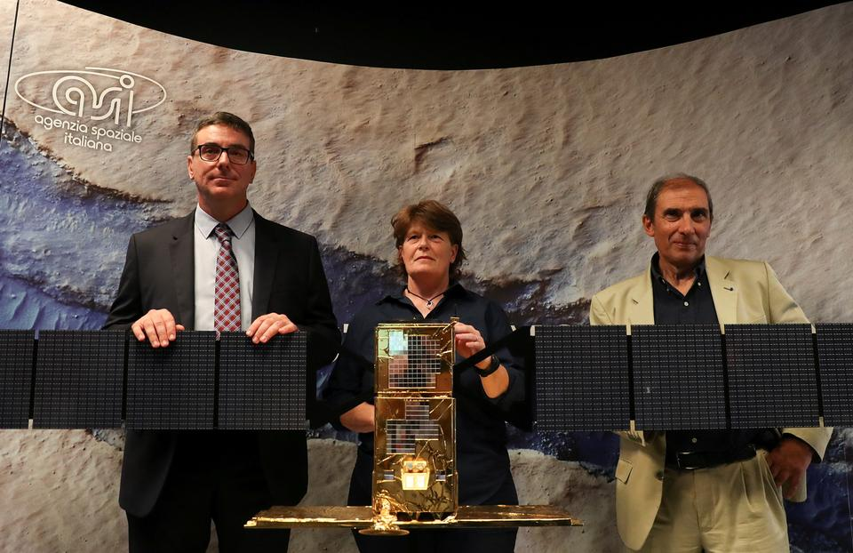 Scientists Roberto Orosei (L), Elena Pettinelli (C) and Enrico Flamini pose near a replica of the Cosmo Sky Med satellite before a news conference where they announce the first-time detection of liquid water on Mars.