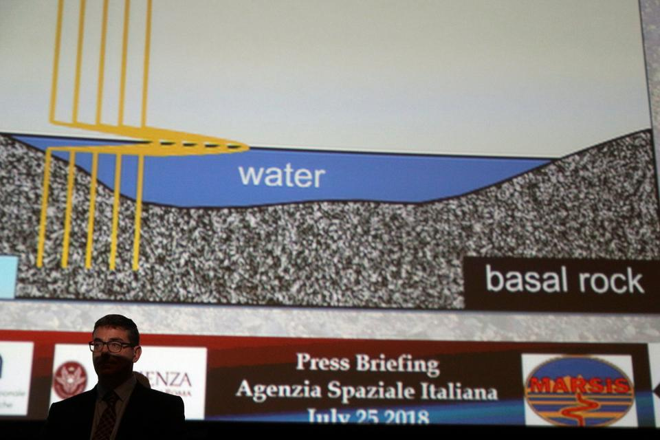 Italian astrophysicist Roberto Orosei, right, meets the media during a press conference at the Italian Space Agency headquarters,in Rome, Wednesday, July 25, 2018. A huge buried lake of salty water appears to be hiding below the surface of Mars, raising the possibility of finding life.