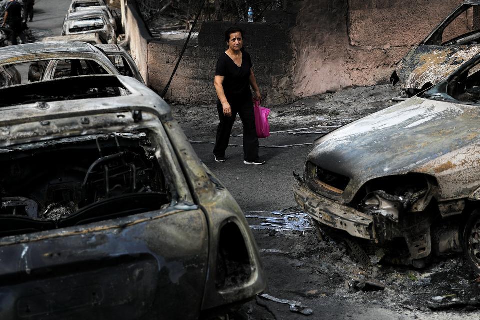 A woman walks among burnt cars following a wildfire at the village of Mati, near Athens, Greece, July 24, 2018.