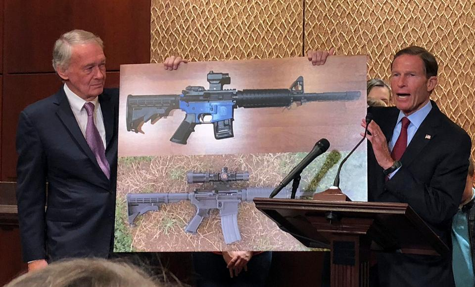 Senator Edward Markey, D-Mass. (L) and Senator Richard Blumenthal, D-Ct., display a photo of a plastic gun on July 31, 2018, on Capitol Hill in Washington. Democrats are calling on President Donald Trump to reverse an administration decision to allow a Texas company to make blueprints for a 3D-printed gun available online.
