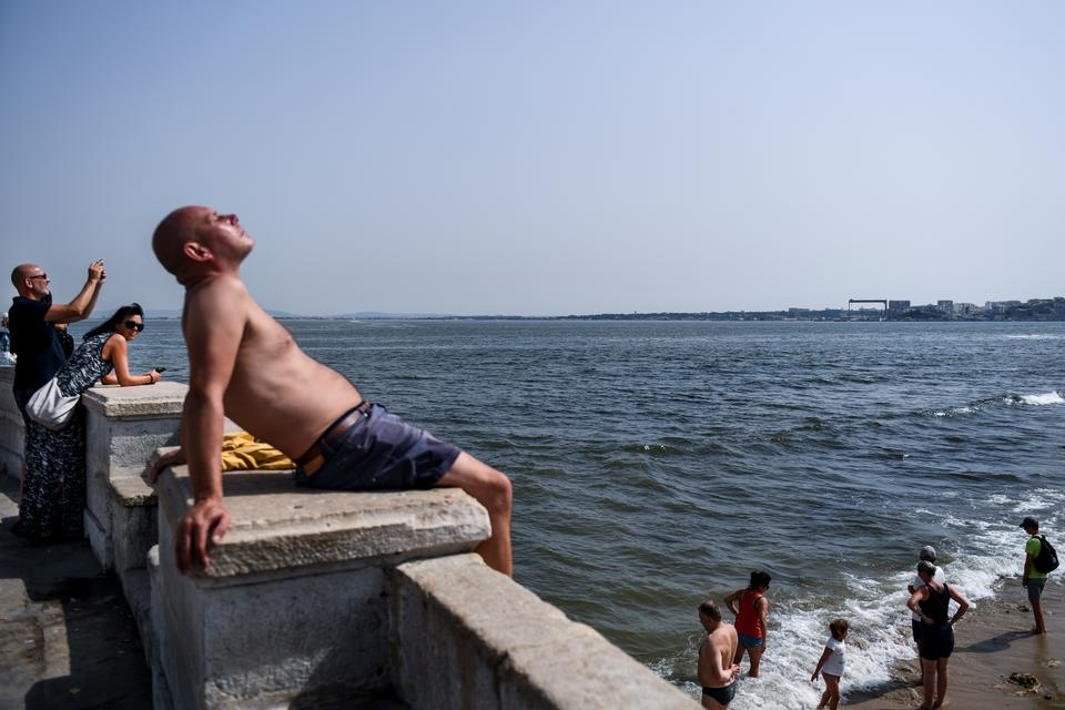 A man sunbathes as others cool off in Tagus River at Ribeira das Naus in Lisbon on August 3, 2018.