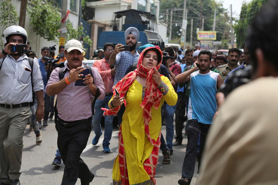 A woman whose brother was killed inside the residence of Farooq Abdullah argues with Indian security officers outside the residence, on the outskirts of Jammu,  August 4, 2018.