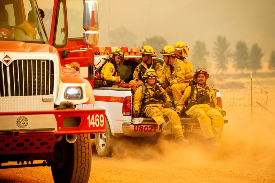 Firefighters ride in the back of a pickup truck while battling the Ranch Fire on New Long Valley Rd near Clearlake Oaks, California, on Saturday, August 4, 2018. The Ranch Fire is part of the Mendocino Complex, which is made up of two blazes, the River Fire and the Ranch Fire.