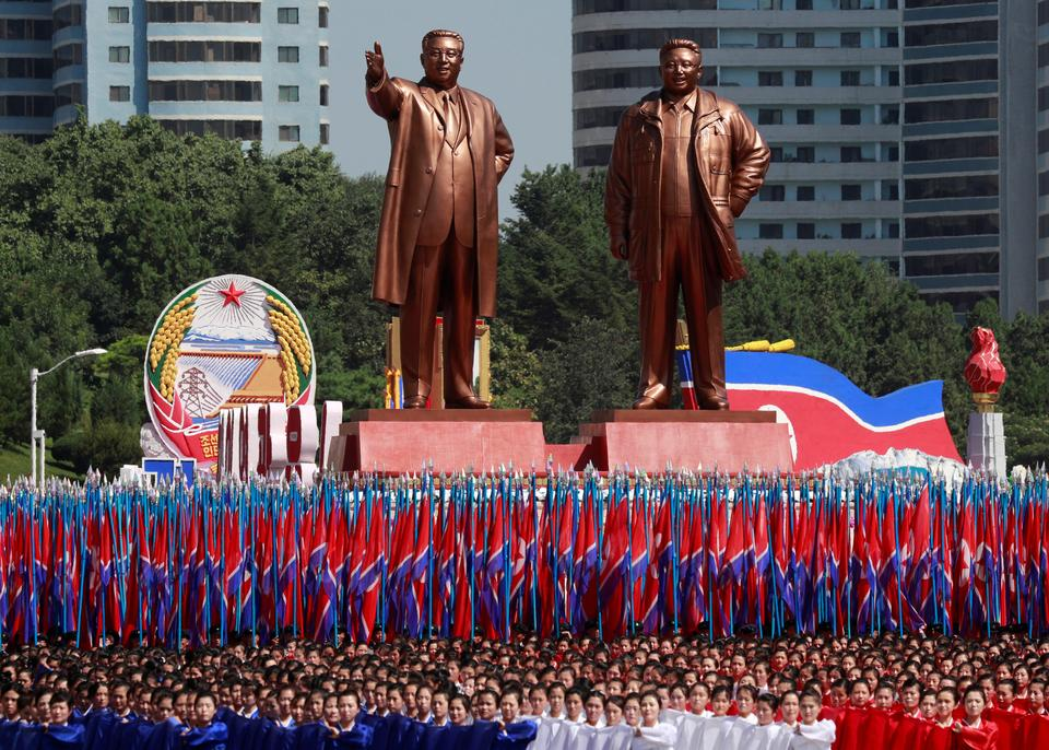 People carry flags in front of statues of North Korea founder Kim Il-sung (L) and late leader Kim Jong-il during a military parade marking the 70th anniversary of North Korea's foundation in Pyongyang, North Korea, September 9, 2018.