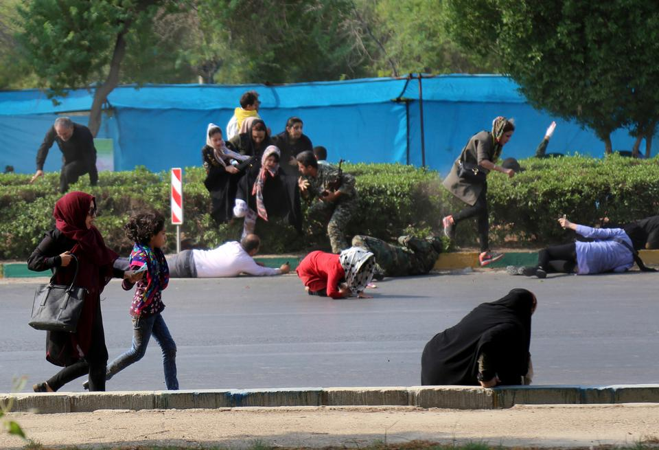In this photo provided by Mehr News Agency, civilians try to take shelter in a shooting, during a military parade, marking the 38th anniversary of Iraq's 1980 invasion of Iran, in the southwestern city of Ahvaz, Iran.