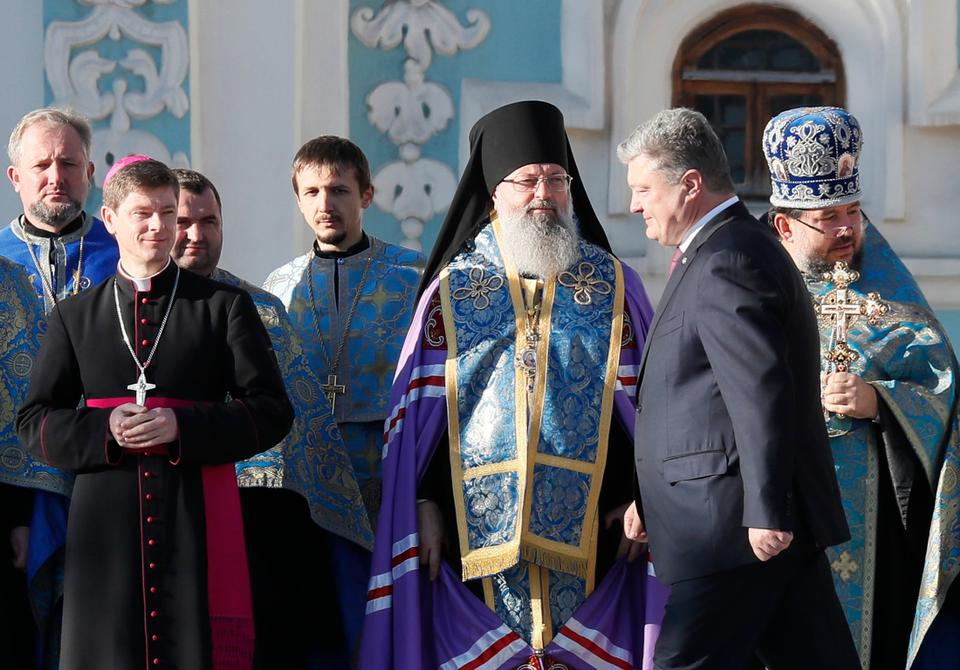 Ukraine's President Petro Poroshenko (2nd R) walks past clergymen during a mass prayer to express gratitude to Istanbul-based Ecumenical Patriarchate for granting approval to establish the country's independent, or