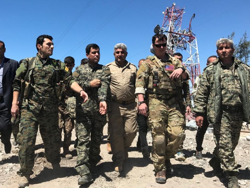 A US military commander (2nd R) walks with YPG militants at the group's headquarters that were hit by Turkish air strikes in Mount Karachok, near Malikiya, in northern Syria on April 25, 2017.
