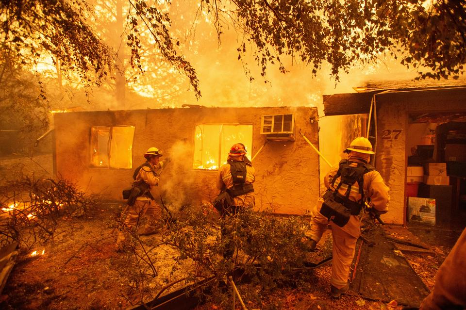 Firefighters battle wildfires in Paradise, California on November 11, 2018.