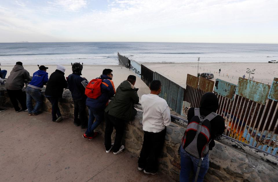 A group of Central American migrants look towards the border structure separating San Diego from Tijuana on November 14, 2018, in Tijuana, Mexico.