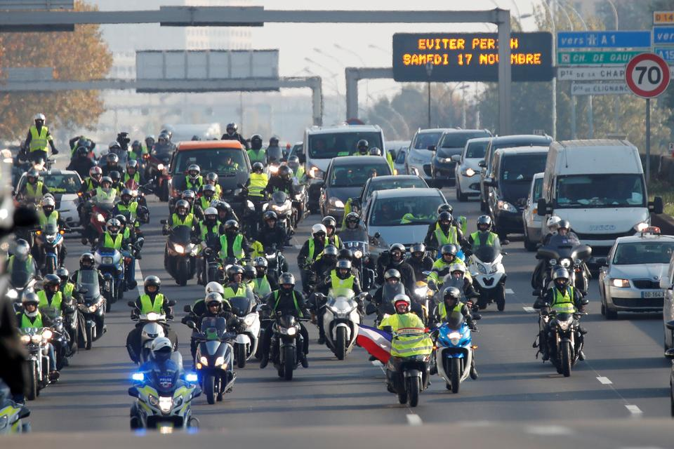 Motorcyclists wearing yellow vests, a symbol of a French drivers' protest against higher fuel prices, move a a snail's pace as they block the ring road in Paris, France, November 17, 2018.