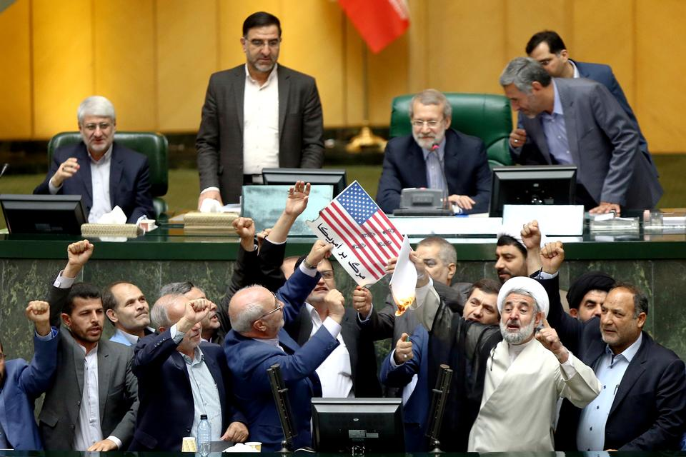 Iranian lawmakers burn two pieces of paper representing the US flag and the nuclear deal at the parliament in Tehran on May 9, 2018.