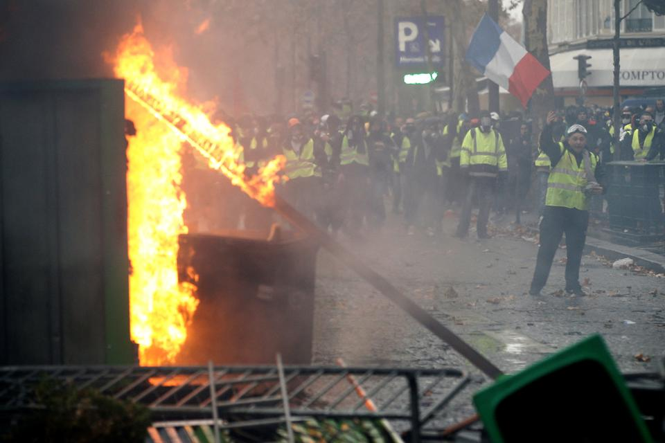 Protesters wearing yellow vests, a symbol of a French drivers' protest against higher diesel taxes, stand near a burning barricade as they face off with riot police during clashes in Paris, France, December 1, 2018.