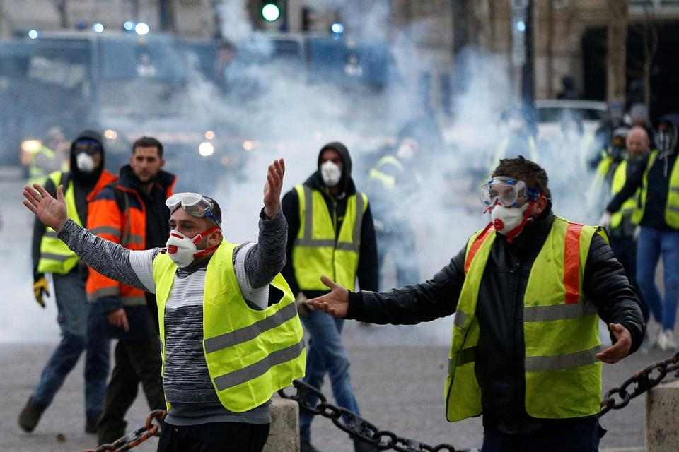 Protesters wearing yellow vests, a symbol of a French drivers' protest against higher diesel taxes, face off with French gendarmes during clashes at the Place de l'Etoile in Paris, France, December 1, 2018.