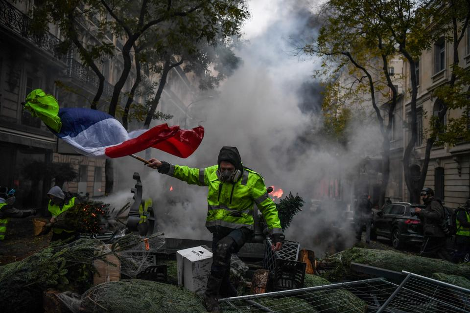 A demonstrator holds a French flag during a protest of Yellow vests in Paris, France on on December 1, 2018.