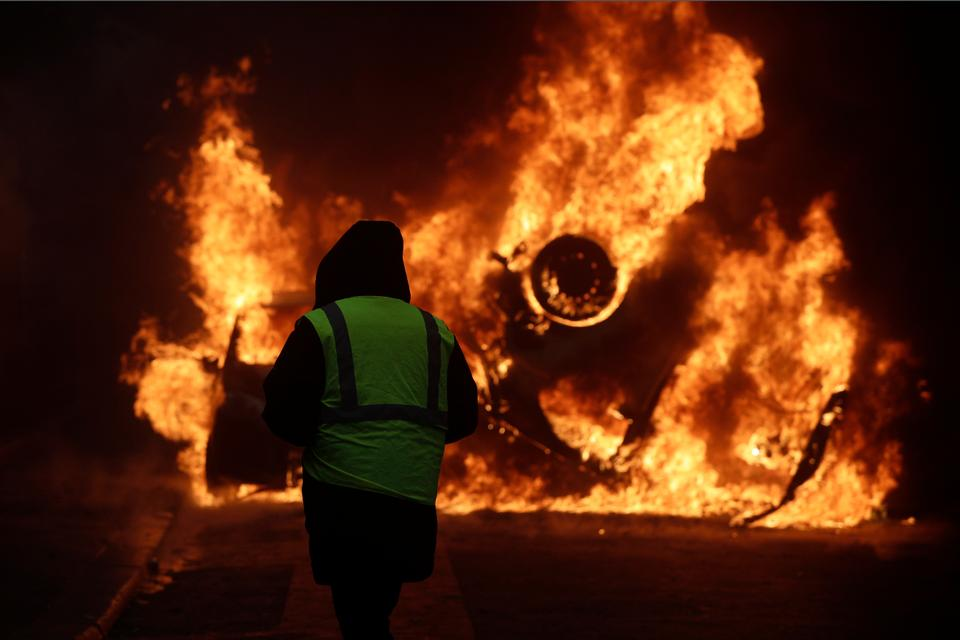 A demonstrator watches a burning car near the Champs-Elysees avenue during a demonstration on Dec.1, 2018 in Paris.